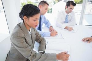 squadra di affari che scrive le idee di brainstorming nel loro blocco note foto