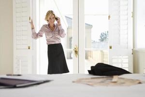 donna in piedi vicino alla finestra, utilizzando il telefono cellulare, sorridente foto