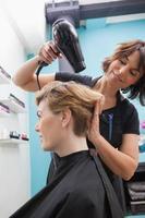 parrucchiere che asciuga i capelli dei clienti foto