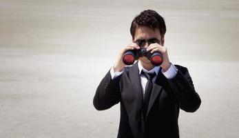 l'uomo d'affari all'aperto esamina il binocolo foto