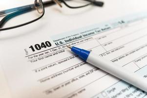 1040 modulo di dichiarazione dei redditi individuale primo piano e occhiali foto