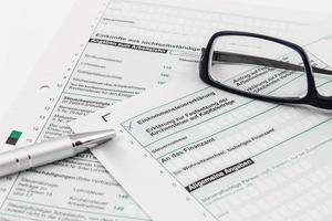 forma di dichiarazione dei redditi con penna a sfera e occhiali foto