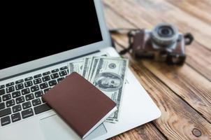 passaporto con noi dollari sul computer portatile foto