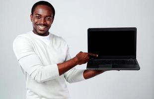uomo africano che mostra lo schermo in bianco del computer portatile