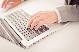 primo piano delle mani dell'uomo d'affari che scrivono sul computer portatile foto
