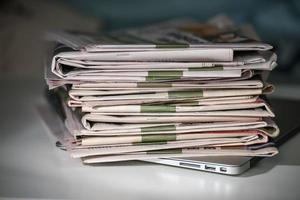 pila di giornali, posizionata su un computer portatile foto