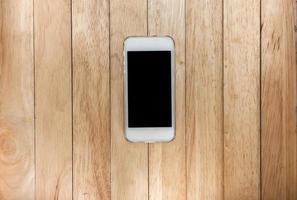 Smart Phone bianco con lo schermo isolato sulla vecchia scrivania di legno. foto