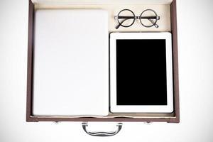 vicino tablet bianco, laptop e occhiali in valigetta foto