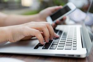 primo piano della mano della donna di affari che scrive sulla tastiera del computer portatile foto