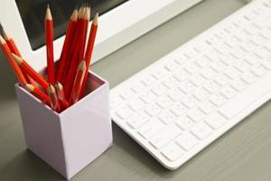 matita rossa sul tavolo con il computer foto