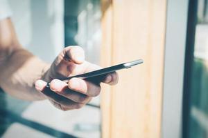 smartphone in bianco che tiene in mano maschile foto