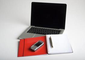 telefono, laptop e taccuino vuoto foto