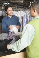 proprietario mostrando magliette lavate a secco al cliente al bancone foto