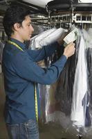 proprietario organizza abiti su rotaia in lavanderia foto