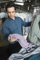 proprietario controlla camicie al bancone in lavanderia foto