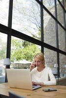 la donna di affari parla sullo smartphone e guarda allo schermo del netbook foto