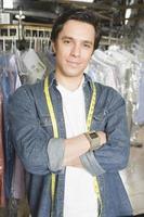 proprietario fiducioso maschio in piedi braccia incrociate in lavanderia foto