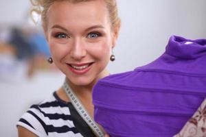 stilista sorridente che ripara vestito sul manichino in uno studio