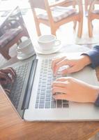 spazio di lavoro con laptop e tazza di caffè sul tavolo di legno foto