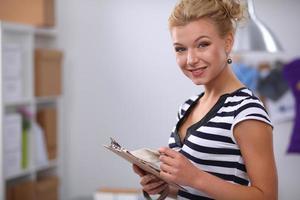 stilista sorridente in piedi vicino al manichino in ufficio