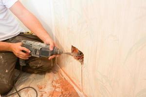 elettricista che collega una nuova presa di corrente in una proprietà residenziale. foto
