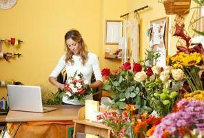 una fioraia al lavoro nel suo negozio foto