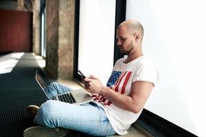 messaggio di testo digitante dello studente attraente dei pantaloni a vita bassa sul suo smartphone foto