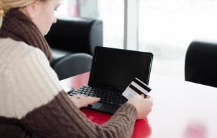 donna della mano del primo piano che per mezzo del computer portatile e della carta di credito, acquisto online