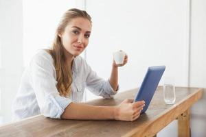 bella bionda con il caffè mentre si utilizza il tablet foto