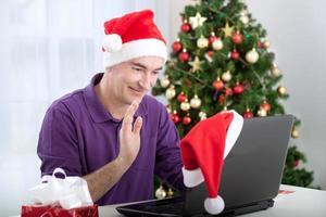 uomo anziano con cappello di Babbo Natale a parlare con la famiglia agitando foto