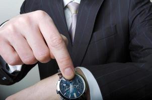 uomo d'affari che punta al suo orologio foto