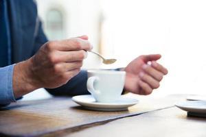 mani del `s dell'uomo d'affari con caffè foto