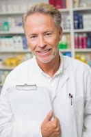 farmacista senior che tiene una lavagna per appunti foto