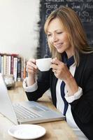 donna di affari che utilizza computer portatile nel caffè foto