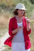 donna rilassata di invecchiamento che gode dell'estate che cammina nella campagna