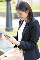 giovane dirigente aziendale asiatico femminile facendo uso della compressa foto