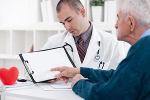 uomo anziano di consulenza con il medico foto