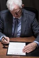 uomo firma il testamento foto