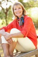 donna senior che si siede all'aperto sul banco foto