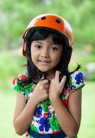 bambini asiatici che utilizzano casco nel parco verde foto