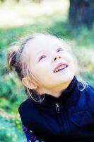 ragazza che osserva in su e che sorride foto