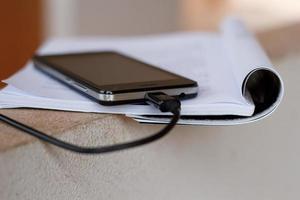 ricarica del dispositivo mobile smartphone messa sul libro. foto