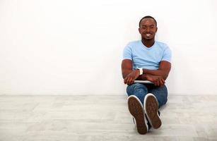 uomo africano felice che si siede con il computer portatile