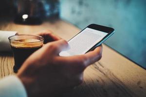 tazza di caffè e ragazza che per mezzo del suo telefono astuto foto