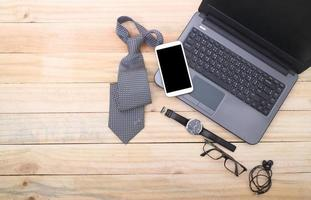posto di lavoro dell'ufficio con il computer portatile e lo Smart Phone sulla tavola di legno foto