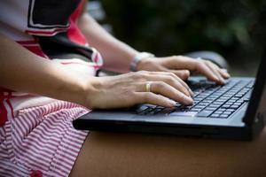 la donna passa il primo piano facendo uso del computer portatile nel parco foto