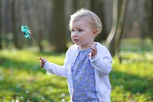 ragazza del bambino che gioca con il giocattolo della girandola nella foresta foto
