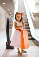 bambina sorridente graziosa con il sacchetto della spesa in centro commerciale