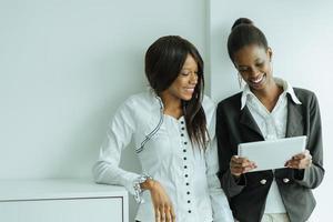 due colleghi che parlano dei contenuti su un tablet pc foto