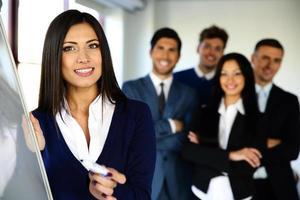 sorridente squadra di affari con lavagna a fogli mobili foto